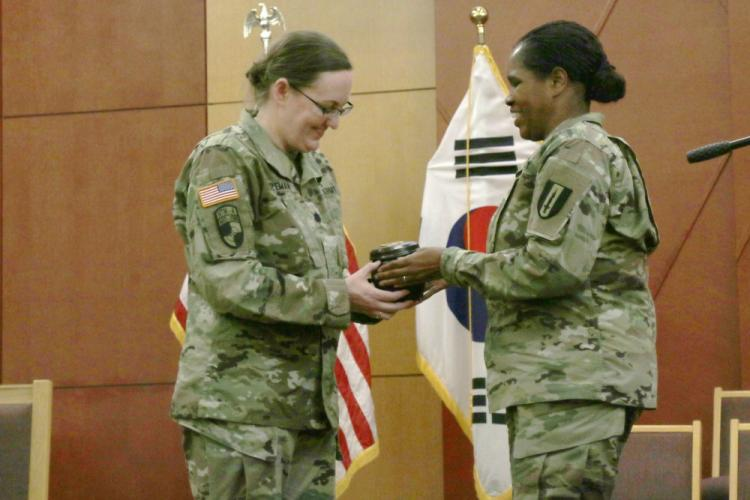 U.S. Army Lt. Col. Cora Henry, Operations officer, 1st Signal Brigade, Eighth Army, gives a gift to Lt. Col. Laura Bozeman, 2nd Infantry Division Equal Opportunity manager, March 25, 2019, Freedom Chapel, Camp Humphreys, Republic of Korea. The gift was given to Bozeman in appreciation for delivering a speech during Women's History Month. (U.S. Army photo by Pvt. Kaden D. Pitt)