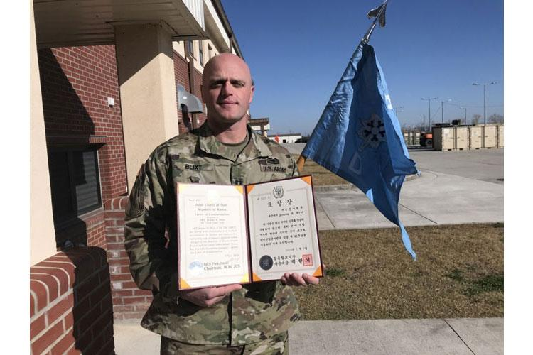 Cpt Jeremy Blixt, commander of D Co., 3rd Brigade Engineer Battalion, 3rd Armored Brigade Combat Team, 1st Cavalry Division poses with his guideon and the Korean War Michaelis Award, that he received at the 41st Combined Forces Command Foundation Ceremony, at Camp Humphrey, Republic of Korea, Nov. 14, 2019. (Photo by Staff Sgt. Jacob Kohrs)