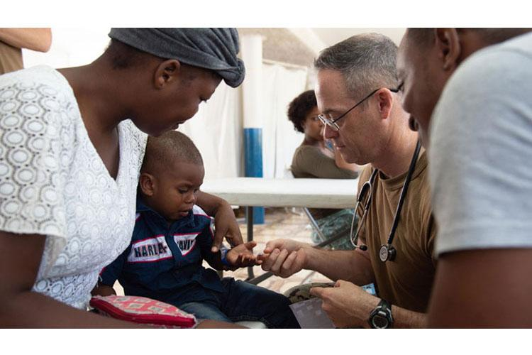 U.S. Navy Capt. Michael Sullivan, a pediatrician assigned to the hospital ship USNS Comfort, gives a sticker to a two-year-old boy after examining his skin infection at a temporary medical treatment site in Port-Au-Prince, Haiti. (U.S. Navy Photo by Mass Communication Specialist 3rd Class Maria G. Llanos)