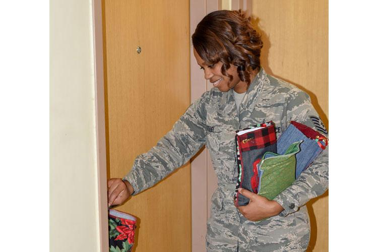 U.S. Air Force Technical Sgt. Chelsea Steel, 8th Civil Engineer Squadron Airman dorm leader, places a stocking full of candy and gifts on a dorm resident's door handle at Kunsan Air Base, Republic of Korea, Dec. 11, 2019. The ADL's placed stockings on over 500 doors in the building while many residents were at work.