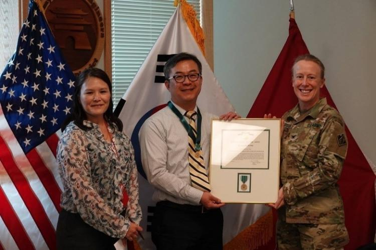 U.S. ARMY GARRISON - YONGSAN, Korea -- U.S. Army Corps of Engineers, Far East District (FED) Commander, Col. Teresa Schlosser, along with Engineering Division Chief, Pamela Lovasz , present, Dr. Jay Pak, geotechnical and environmental engineering branch chief, with a commander's award for his hard work and dedication to the district during his almost four year tenure at the district, and pose for a photo. (Courtesy photo: Jay Pak)
