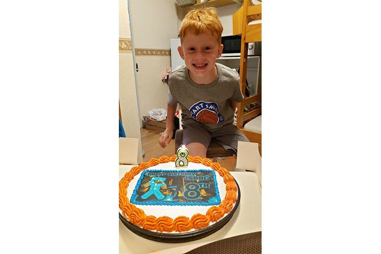 On Aug. 28, Isaac Morford, 8, poses with his custom Minecraft cookie baked by the Commissary and decorated by Yokota Bakery by special request from his mother, Mandy. The Morford family recently moved to Japan and lost track of time while unpacking and setting up their home and the start of a new school year. (Photo by Mandy Morford)