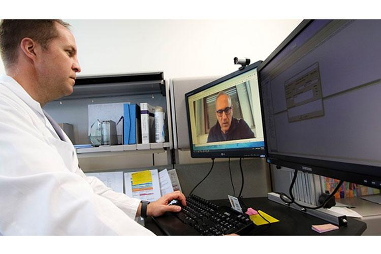 U.S. Air Force Lt. Col. Brendt Feldt, a surgeon at Landstuhl Regional Medical Center's Ear, Nose and Throat Clinic, conducts a virtual health appointment via synchronous video. Innovations in virtual health, particularly telehealth, have been essential to continuing quality care for beneficiaries during the COVID-19 pandemic. DHA has made temporary changes to TRICARE regulations to expand telehealth care and prevent the spread of COVID-19. (Photo by Marcy Sanchez)