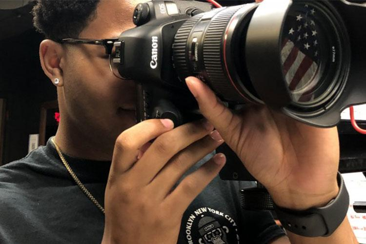 Summer hire student William Hamilton takes a photo at the VISC photo studio. Area IV summer hires are given hands-on work experience to prepare them for the future. (Photo Credit: Xiomara Bradden)