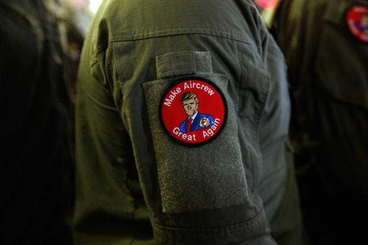 "A servicemember wears a patch that says ""Make Aircrew Great Again"" while listening to President Donald Trump speak at a Memorial Day event aboard the USS Wasp on Tuesday, May 28, 2019, in Yokosuka, Japan. The patch includes a likeness of Trump. EVAN VUCCI/AP"