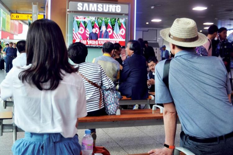 People at watch television coverage of the historic summit between President Donald Trump and North Korean leader Kim Jong Un at Seoul Station in South Korea, Tuesday, June 12, 2018. SETH ROBSON/STARS AND STRIPES