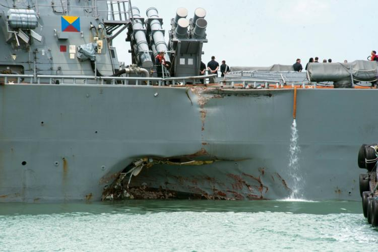 Damage to the left side is visible as the destroyer USS John S. McCain steers towards Changi Naval Base, Singapore, following a collision with a merchant vessel on Aug. 21, 2017. The Navy is replacing touch-screen throttles and helms on destroyers with hand-held ones after determining that the McCain's controls caused confusion that contributed to the collision. JOSHUA FULTON/U.S. NAVY