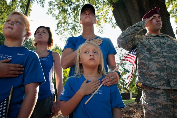 Six-year-old Sydney Badwound, center, and her mother Stephanie Badwound, an Army spouse, join others in rendering a salute during a ceremony on Sept. 11, 2014, at Fort Bragg in North Carolina on the anniversary of Sept. 11, 2001. CAROLYN COLE/LOS ANGELES TIMES/TNS