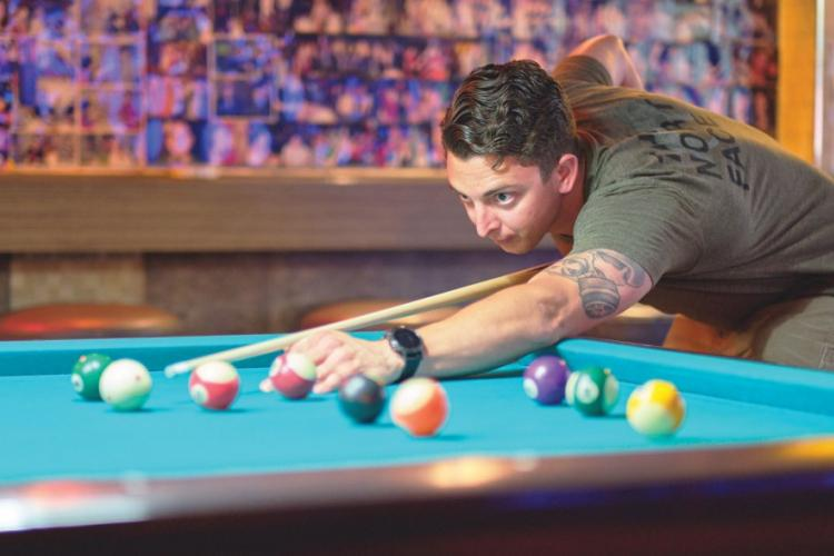 Air Force Staff Sgt. Cody Meyer shoots pool at Kelly's Bar just outside Osan Air Base, South Korea, in June. The U.S. military has extended its curfew suspension for most U.S. forces in South Korea. MATTHEW KEELER/STARS AND STRIPES