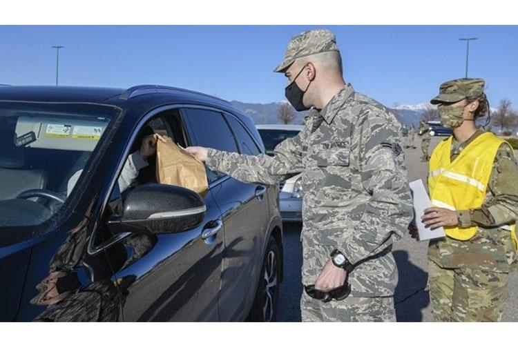 PETERSON AIR FORCE BASE, Colo. – Airman 1st Class Grant Alvarez, 21st Logistics Readiness Squadron (left) and Capt. Lorna Neeley, 21st Medical Group, assist customers at the new drive-thru pharmacy located at the Peterson base exchange parking lot. This new procedure is being used to help prevent the spread of COVID-19. (Air Force photo by Craig Denton)