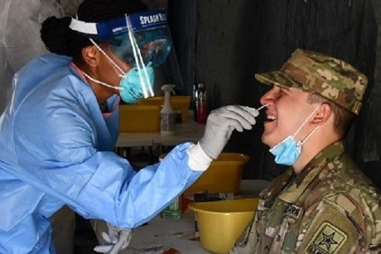 Army Sgt. Toni-Moi Dewar, noncommissioned officer in charge of the Kenner Army Health Clinic's Active Duty Clinic performs a COVID-19 swab of a soldier at Fort Lee in Virginia. (U.S. Army photo)