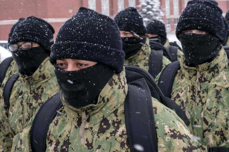 In a January, 2019 photo, recruits walk in formation wearing neck gaiters during a snowstorm at Recruit Training Command in Great Lakes, Ill.. SPENCER FLING/U.S. NAVY