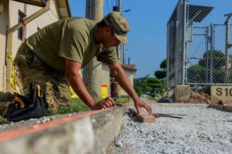 Staff Sgt. Jimmy Noriega, 8th Civil Engineer Squadron heavy equipment and pavement craftsman, measures the sidewalk for construction at Kunsan Air Base, Republic of Korea, Aug. 23, 2020. This sidewalk construction is part of the final stages of a larger road work project located in front of the Community Bank. (U.S. Air Force photo by Senior Airman Jessica Blair)