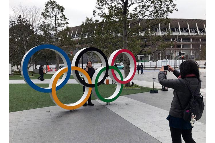 A visitor to the Japan Olympic Museum poses with the Olympic rings near the new National Stadium in Tokyo, Jan. 22, 2020. The stadium will host many events, including the opening and closing ceremonies, for the Summer Games. HANA KUSUMOTO/STARS AND STRIPES