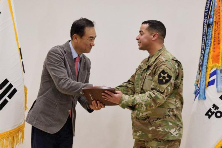 Pyeongtaek Mayor Jung Jang-seon presents a plaque of appreciation to Army Spc. Jonathan Roman Rios in Pyeongtaek, South Korea, Thursday, March 28, 2019. MATT KEELER/STARS AND STRIPES