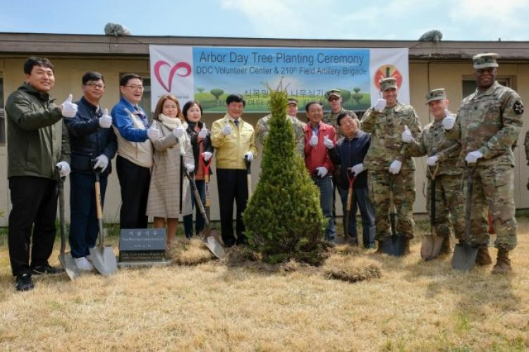 The 210th Field Artillery Brigade and Dongducheon City leaders take a group photo together after planting a new tree during an Arbor Day Tree Planting Ceremony at Camp Casey, Republic of Korea, April 16. The 210th FAB command teams and local community leaders gathered for the twelfth annual tree planting ceremony which symbolized the strong partnership that exists between both organizations. (U.S. Army photo by Capt. Daniel Parker) (Photo Credit: Capt. Daniel Parker)