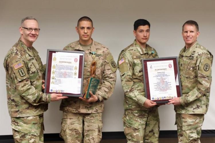 Brig. Gen. Dennis LeMaster, RHC-P commanding general, and RHC-P Command Sgt. Maj. Clark Charpentier present Staff Sgt. Christopher Velazquez and Spc. Jonathan Mossett with the NCO and Soldier's creeds at the 2019 RHC-P Best Warrior award ceremony. Velazquez won the NCO category and Mossett won the Soldier category. (Photo Credit: U.S. Army)