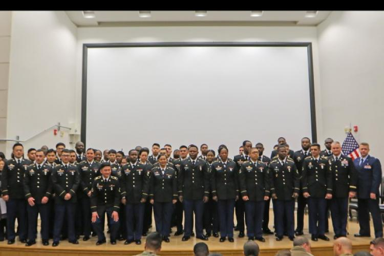 Fifty two members of U.S. Forces Korea stand on the stage of the General Paik Auditorium inside U.S. Forces Korea headquarters on Camp Humphreys, South Korea, Feb. 13. Minutes before, the group all became United States citizens after being sworn in. (Photo Credit: Cpl. Moon, Jihwan)