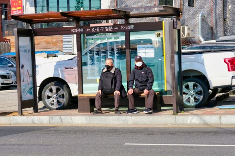 People wait for a public bus outside Camp Humphreys, South Korea, March 16, 2020.  MATTHEW KEELER/STARS AND STRIPES