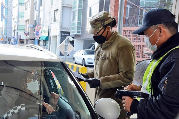 Pvt. Daija Gillam, 22, of the 25th Transportation Battalion, screens drivers before allowing them to enter Camp Walker in the coronavirus-hit city of Daegu, South Korea, Saturday, Feb. 22, 2020. KIM GAMEL/STARS AND STRIPES